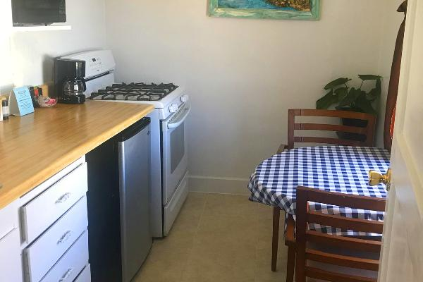 Kitchen with microwave, refrigerator, oven, stove & seating for two.