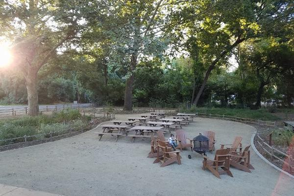 The courtyard features 10 picnic tables and 6 adirondack chairs on decomposed granite, surrounded by a native plant garden and mature trees.