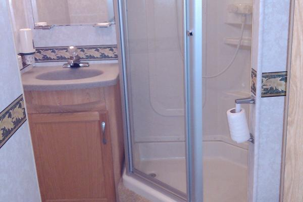 Full Bathroom with corner shower, toilet, sink, vanity/mirror