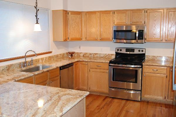 Spacious kitchen with granite counters and wood floors